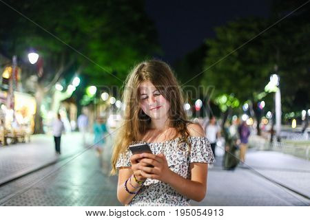Young Cute Blonde And Happy Girl Writing Message On The Phone In The Street With Sincere Look And Tr