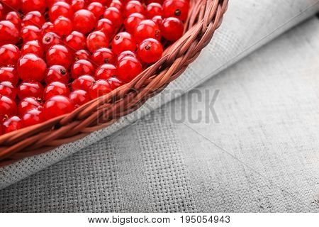 Macro colorful red berries on a grey background. Fresh tasteful currant in a wooden basket. A spacious crate on a light piece of fabric. Fruit ingredient.