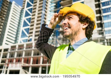 Civil engineer or architect checks progress of construction works at building site of high-riser