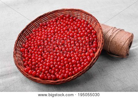Fresh and tasteful red current in a light brown basket close-up. Red berries on a gray background. A coil of thread on a piece of cloth with berries. Healthful vegan diet.