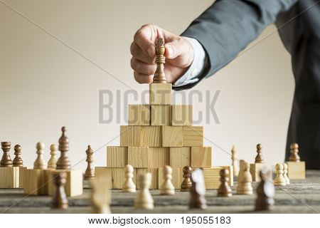 Businessman Placing A Chess Piece On Blocks