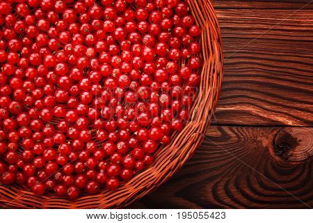 Close-up juicy berries on a bright brown background. Fresh red currant in a crate. A basket full of delicious cranberries. An eco-friendly wooden basket on a table with fresh currant.