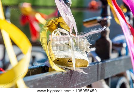 A Closeup Of The Golden Wedding Padlock Covered With White Textile, Ribbons And Artificial Flower On