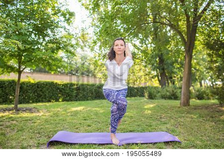 The good-looking woman is practicing yoga on the nature background. The perfect and healthy woman. A charming lady is in a white sweater and blue leggings is doing yoga.