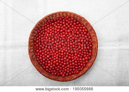 Close-up picture of a brown basket on a silver piece of cloth. A basket filled with tasteful healthful red cranberries. Raw and sour berries on a grey background.