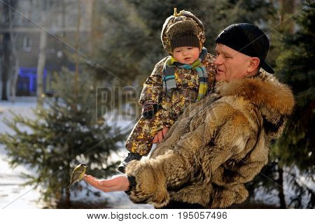 Father and son came to the park in the winter to feed titmouses and pigeons