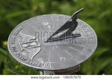 A sundial in a outdoor flower garden
