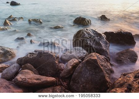 Dramatic rocky coast with seaweed,close up.  Selective focus  of a rocky shoreline at sunset