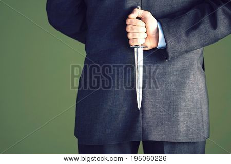 Closeup midsection of a businessman holding knife behind back against green background