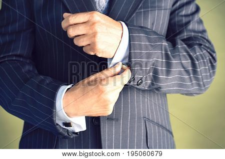 Closeup midsection of a businessman in suit buttoning cuff sleeves