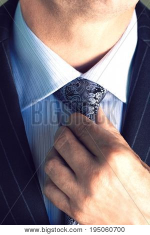 Closeup midsection of a businessman in suit adjusting necktie