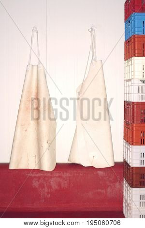 Closeup of butcher's aprons hanging on wall next to stack of crates