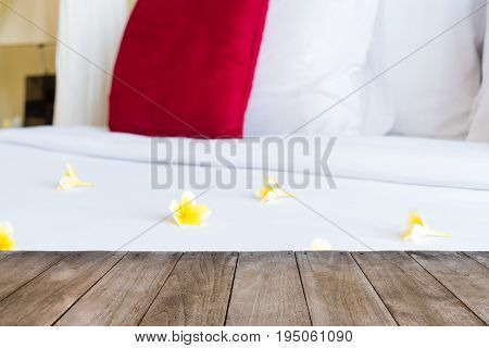Perspective Empty Wooden Table In Front Of Hotel Bed With Flowers