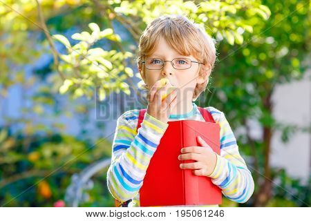 Cute little kid boy with glasses, books, apple and backpack on his first day to school or nursery. Child outdoors on warm sunny day, Back to school concept