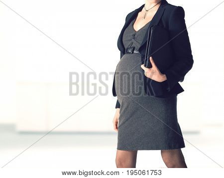 Midsection of a pregnant businesswoman walking with folder against blurred background