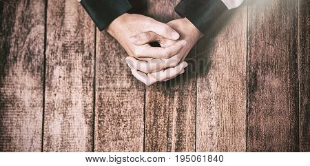 Praying hands of woman on wooden table