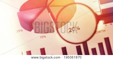 flared figure against close up of magnifying glass on graph chart