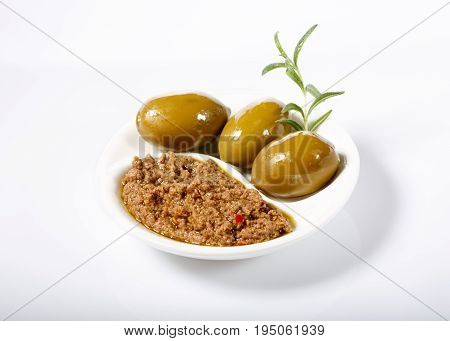 Tapenade - spicy olive paste made from green olives and red hot chilli pepper. On white. Copy space.