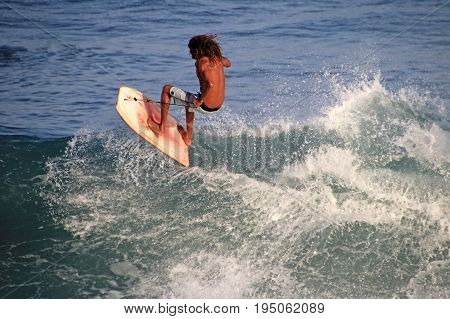 Matchless boogie boarder standing on the board and surfing, El Zonte beach, El Salvador, Central America