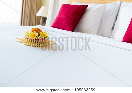 Hotel room with bed and flower arrangement copy space for text