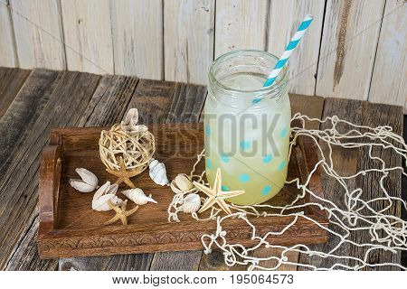 lemonade drink in polka dot mason jar with striped drinking straw and seashells on wooden serving tray