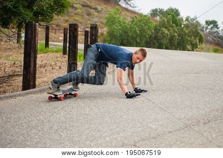 Downhill Skateboarder using gloved hands to skid around the corner from downhill view.