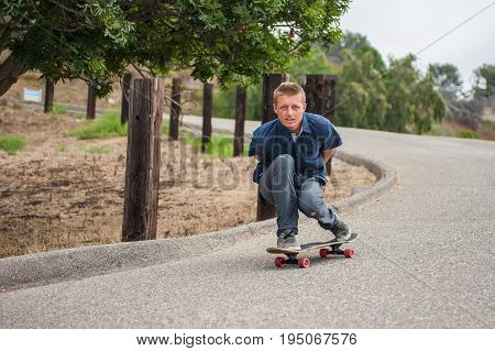 Blond skateboarder crouched low as he gains speed down the declining road.