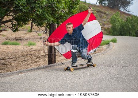 Daredevil skateboarder man holding parachute to control speed as he moves downhill.