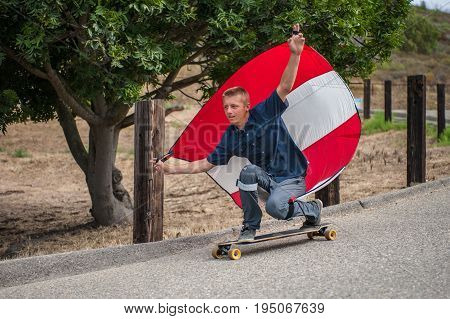 Parachute downhill skateboarder has sail full of wind as he rides goofy foot on his board.