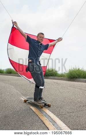 Parachute downhill skateboarder has sail full of wind as he rides the nose of board.