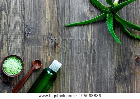 Aloe vera leafs, spa salt and cosmetic clean lotion on wooden background top view.