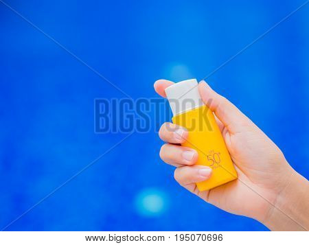 Woman hand holding UV sunscreen bottle by the swimming pool. Vacation and relaxation summer travel concept.