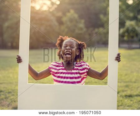 African descent girl is holding frame in a park