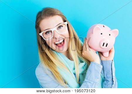 Young woman with a piggy bank on a blue background