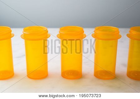 Amber-colored prescription drug vials lined up on white.  Suitable for representing healthcare, insurance, wellness or addiction