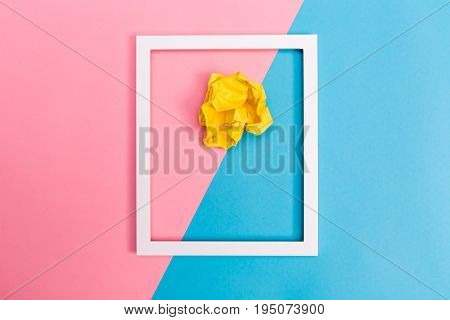 Crumpled paper ball with frame on a bright split tone background