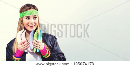 Woman in 1980's fashion holding painted bananas on a white background
