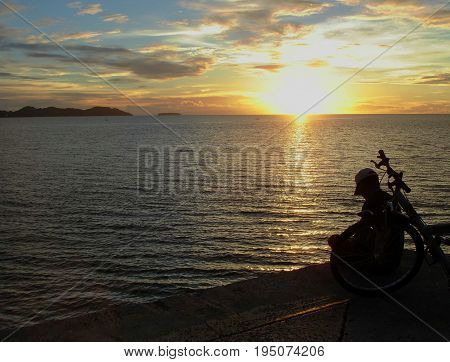 Silhouette of biker at sunset A biker rests by the seaside, silhouetted by a beautiful sunset reflected tin the water