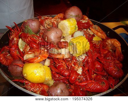 Seafood mix served in a round deep metal platter  Crawfish and boiled shrimp, crawfish prawns corn cob and red potato, red beans and rice