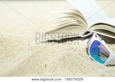 Close up of white sunglasses and book on the beach on warm yellow sand. Turn the page and relax.
