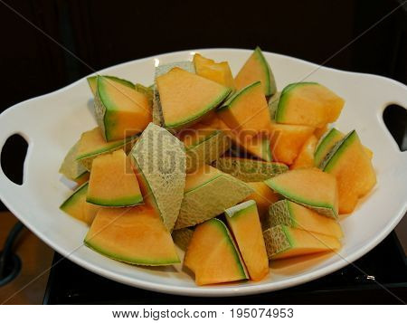 Slices of cantaloupe melon arranged in a round oval plate with handhold