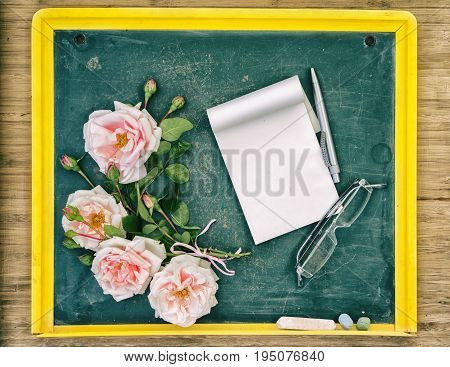 Back to school congrats concept Roses pen glasses and textbook laying on the small chalkboard Top view with copy space on the empty textbook.