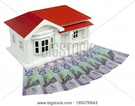 Bungalow villa house model with New Zealand NZ $50 Dollar notes in cash - side view isolated on white background