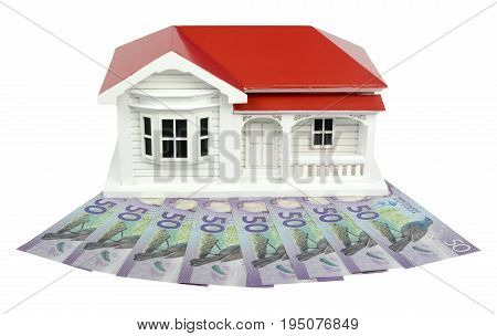Bungalow villa house model with New Zealand NZ $50 Dollar notes in cash - front view isolated on white background
