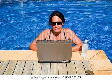 Stressed female executive workaholic working on laptop computer in swimming pool on vacation concentrating on work