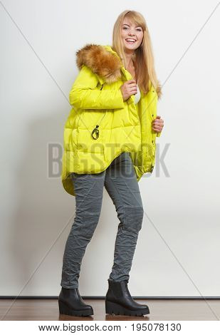 Beautiful smiling young fashionable girl wearing jacket with hood posing. Preparing herself clothes. Fashion in winter time.