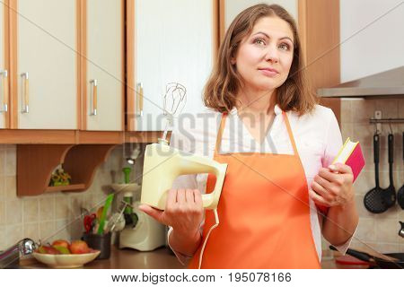 Housewife thinking and planning meal food. Mature woman chef cook with cookbook and mixer.