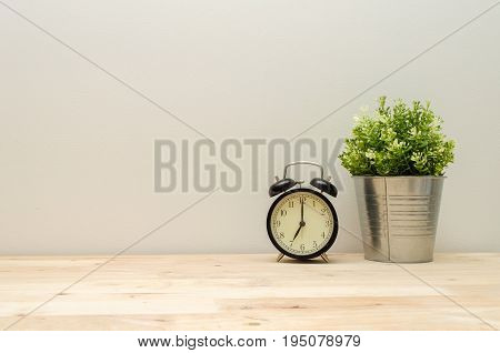 black vintage alarm clock times at 7 o'clock morning and green plant tree in silver pot small minimal decorative on wooden desk and white wall background vintage tone retro style