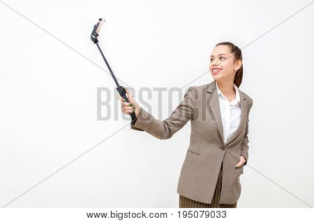 happy young asian business woman in suit beautiful smiling taking selfie with mobile smartphone on selfie stick isolated on white background social media network technology and lifestyle concept
