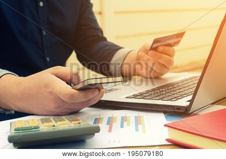 young man holding credit card and using smartphone with report sheet calculator laptop on desk online shopping online payment lifestyle technology finances and economy concept selective focus